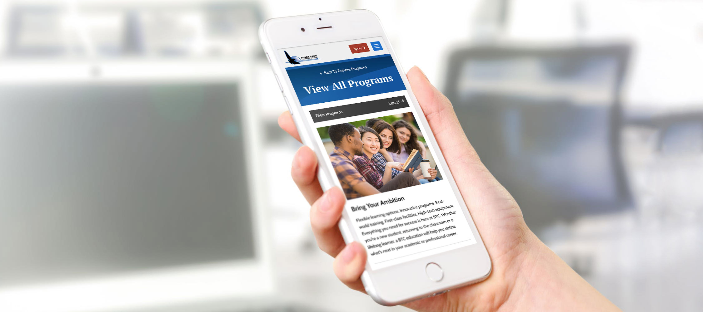 Hand holding mobile phone with Blackhawk Technical College website on screen